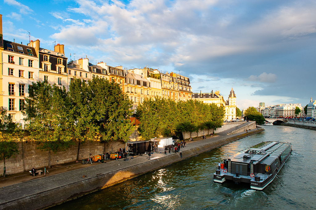 a photo of a film crew working on the banks of the seine river paris france