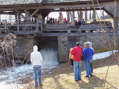 Water flowing across water wheel to power sawmill demonstration