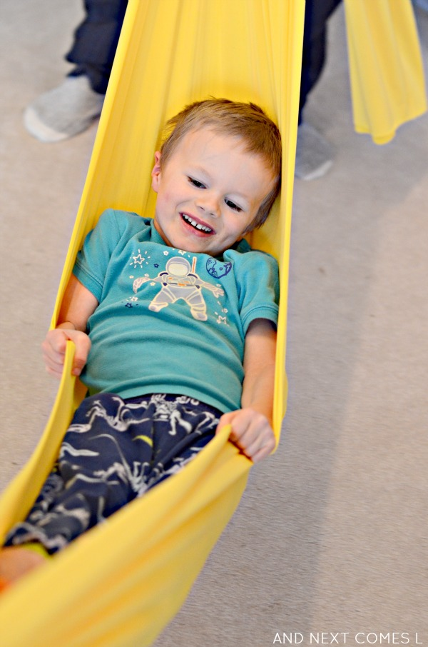 Using a homemade sensory tunnel as a swing from And Next Comes L