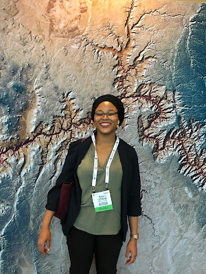 Photo of Kopo Oromeng standing in front of a satellite image of the Grand Canyon
