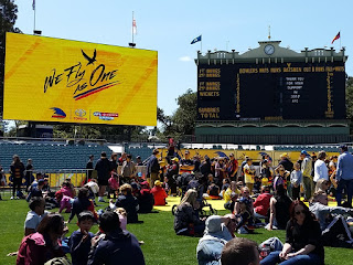 A large video screen and the Adelaide Oval scoreboard are the backdrop for families and fans to gather on the turf . Families are sitting in groups on the lawn or standing near the stage in front of the scoreboard awaiting the arrival of the players.