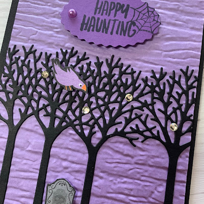 Close up of handmade Halloween card showing tombstone and purple bird sitting in a row of trees
