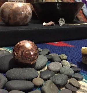 A close up of a copper sphere from Michigan nestled in black beach stones. A bowl of salt water and light candles sit on a cloth-covered journal