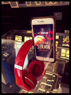 Audiobook The Mars Strain on iPhone resting on glass panel above NASA control board on space shuttle.