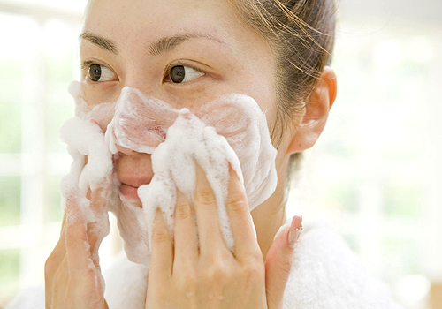 chica aplicando jabón en el rostro