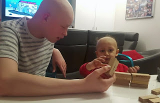 Harri plays with a child in hospital