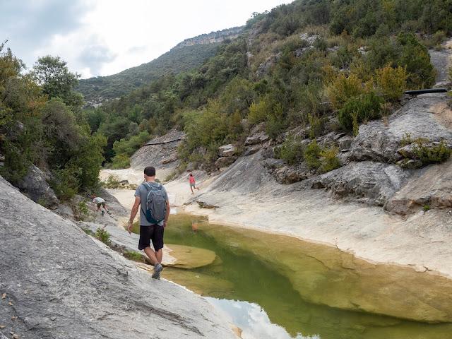 Hombre y niños de espaldas caminando junto a una de las pozas de San Martín (Huesca)