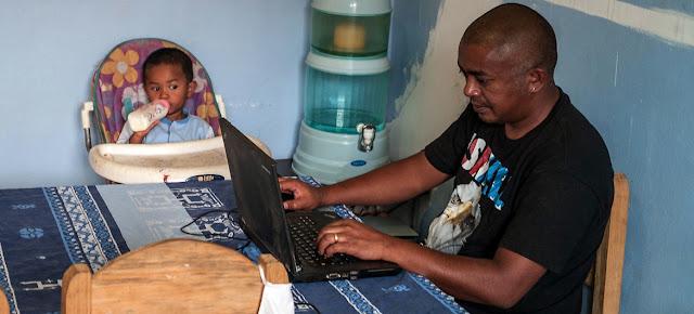 Un hombre cuida a su hijo mientras trabaja desde la casa en Madagascar.Banco Muncial/Henitsoa Rafalia