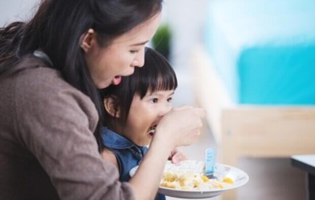 Madre dando de comer a su hija