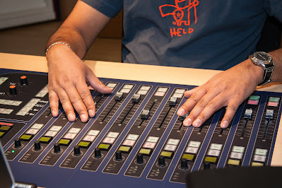 Hands using a mixing desk in a radio studio