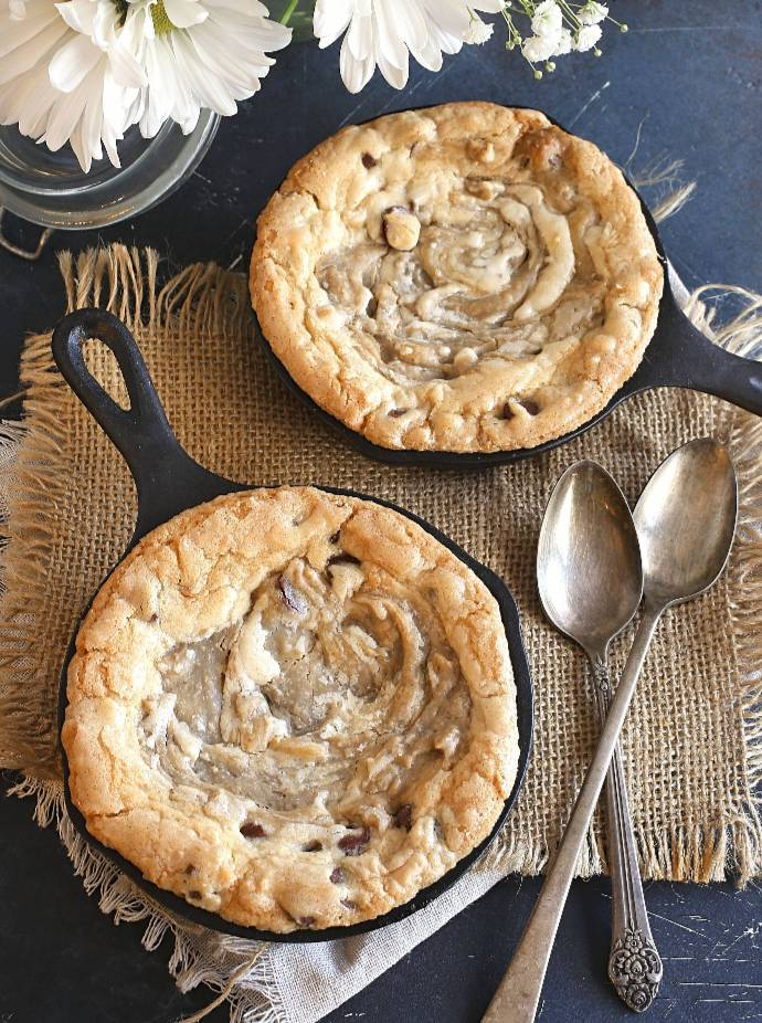 Recipe for individual skillet chocolate chip cookies with a sweet tahini swirl and topped with ice cream and halvah candy.