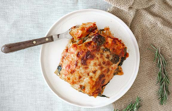 Lasagna on a white plate with rosemary sprigs