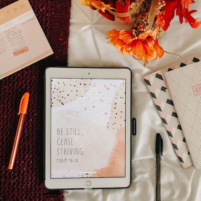Flatlay with iPad, orange flowers, pens, and notebooks.