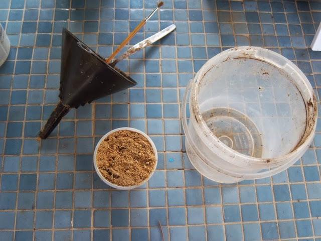 Un envase amplio, un embudo, algo para recoger la tierra, una botella, algo para remover y agua