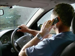 Man talking on mobile phone while driving image