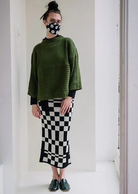 Woman in emerald green sweater and black and white checked skirt