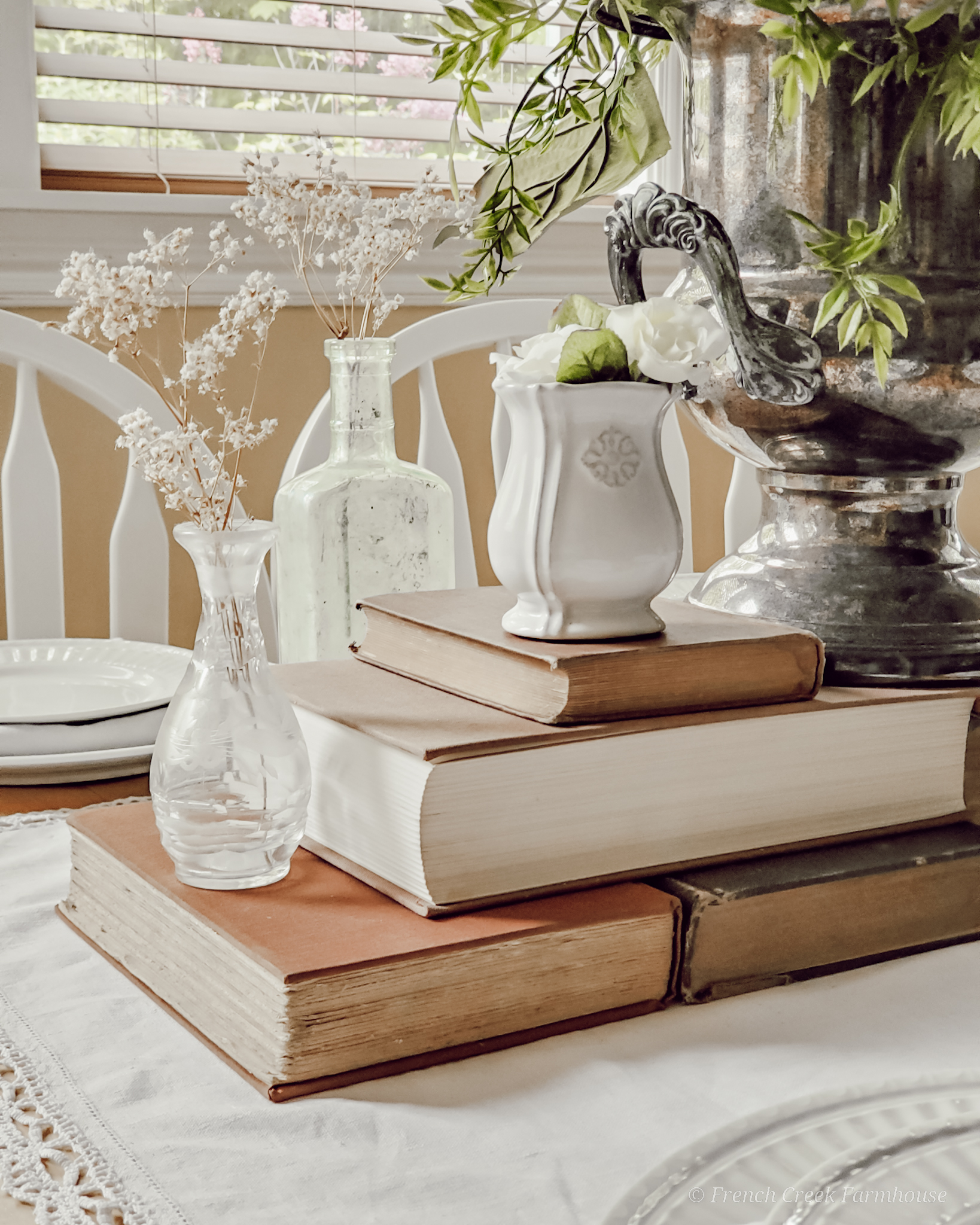 Old books used in a table centerpiece with vintage vases