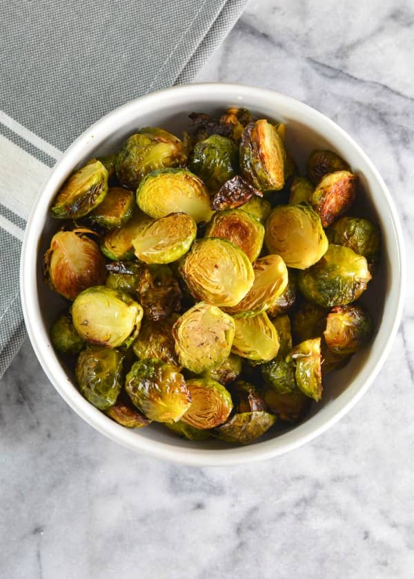 Roasted Brussels Sprouts with Garlic recipe. The secret to crispy quick roasted brussels sprouts with garlic and lemon without becoming mushy or dry. A favorite side dish for Thanksgiving and Christmas from Serena Bakes Simply From Scratch.