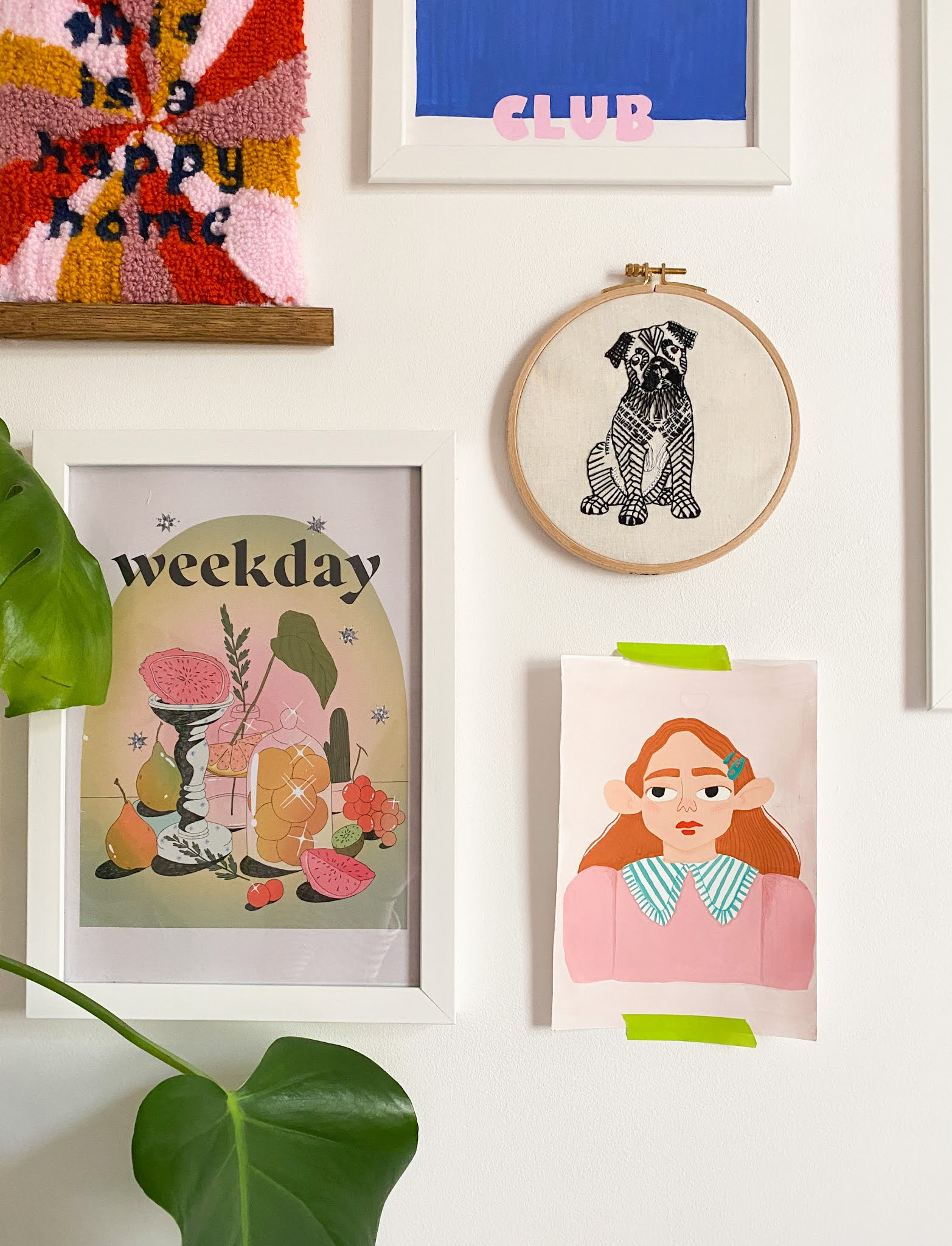 """gallery wall of prints including drawing of red headed girl with large collar, """"weekday"""" print with fruits on platter, embroidery hoop of pug and punch needle wall hanging reading """"this is a happy home"""""""