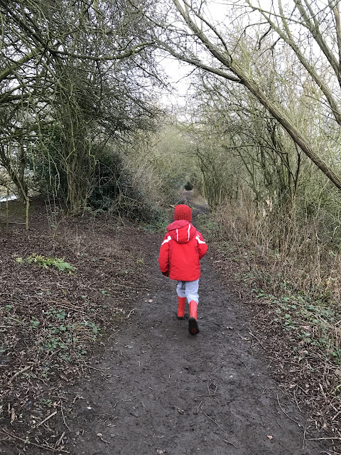 Little boy walking through a muddy wooded area