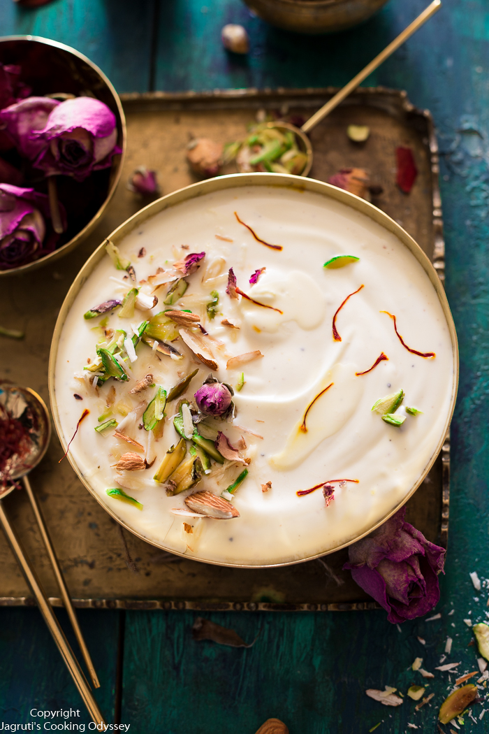 Indian style yogurt based white dessert served in a brass bowl and garnished with green pistachio, rose petals and saffron.