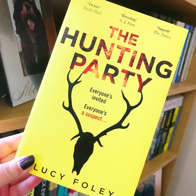 The Hunting Party by Lucy Foley held up in front of bookshelf