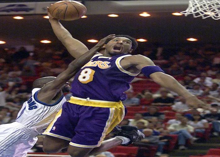 Pemain Los Angeles Lakers, Kobe Bryant berusaha memasukan bola dari penjaga pemain Orlando Magic Darrell Amstrong selama pertandingan NBA di Orlando pada 21 Maret 1999 berlangsung.