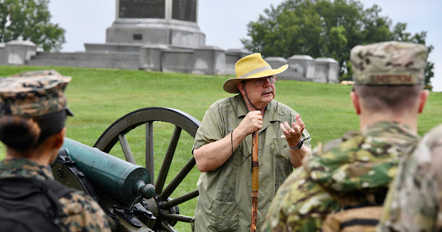 Dr. Dale Smith standing next to a civil war cannon, talking to students.