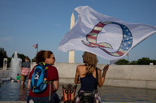 Qanon supporters wait for the military flyover at the World War II Memorial during 4th of July celebrations in Washington, DC.  Evelyn Hockstein/For The Washington Post/Getty Images