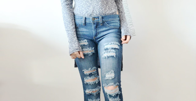 A grunge-chic outfit featuring distressed ripped dark wash skinny jeans from Sneak Peak & Tara Lynn's Boutique, worn with a turtleneck marled split high-low asymmetric long sleeve knit top and lace-up heeled boots.