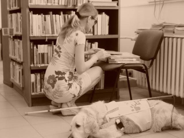 Linda si prohlíží knihy u regálu v knihovně, vedle na podlaze leží vodící pes a bílá hůl
