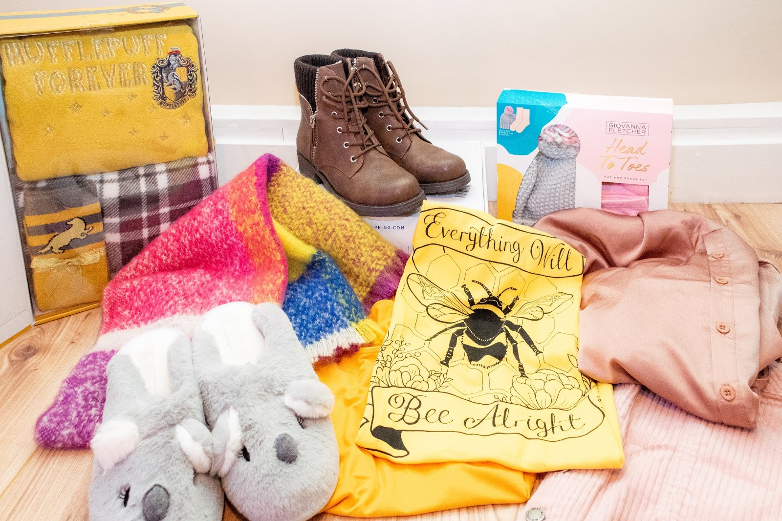 Clothing gifts gathered together: hufflepuff pyjamas, brown boots, colourful scarf, koala slippers, yellow t-shirts, pink skirt, pink silk jumpsuit.