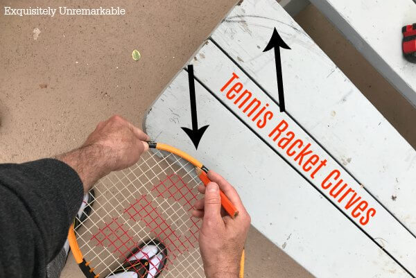 Using a tennis racket to draw a curve on wood with text that says tennis racket curves