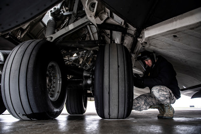 checks the air pressure of a tire on a C-17 Globemaster III