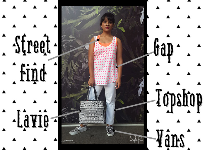 Image of female indian fashion blogger wearing printed plimsols and tote bag with neon crop top and white skinny jeans