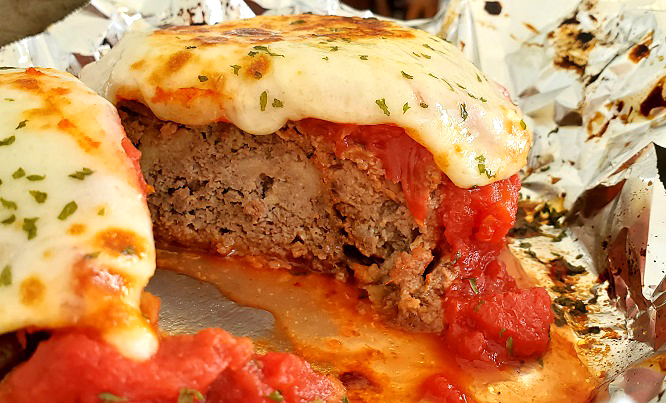 this is a slice of meatloaf made Italian style with melted cheese and marinara sauce on top
