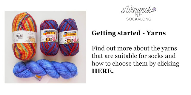 Three balls of multi-coloured sock yarn with a skein of blue yarn underneath, all resting on a white background