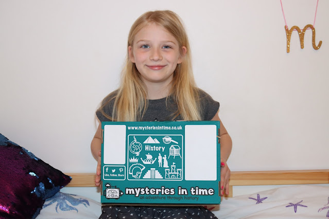 A primary school age child holding a teal and white cardboard history subscription box