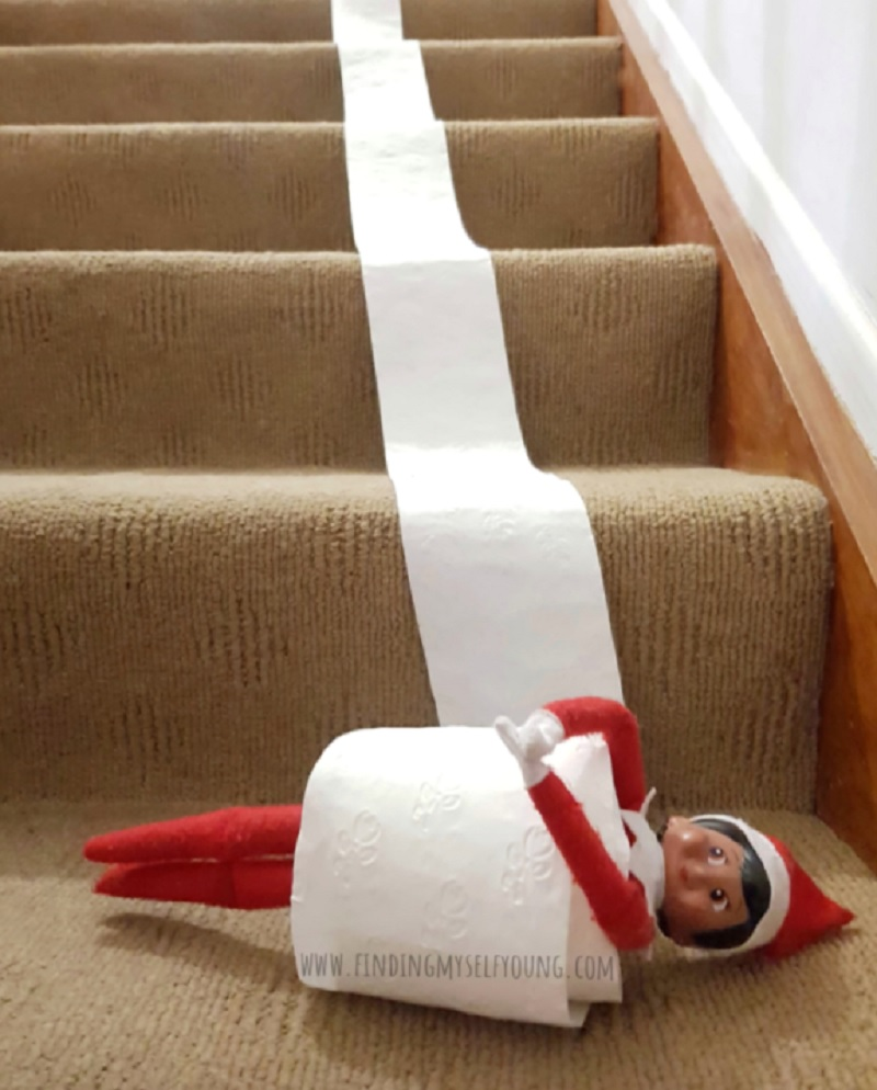 elf rolling down the stairs in a roll of toilet paper