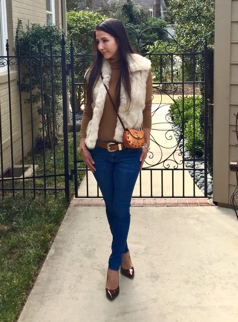 Wearing camel turtleneck with white fur vest and crossbody small orange leather tooled bag, skinny jeans and tortoise heels.