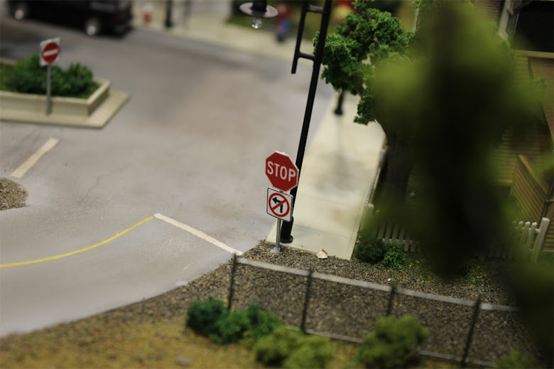 Detailed view of a stop sign and no left turn sign installed at an intersection in a downtown scene
