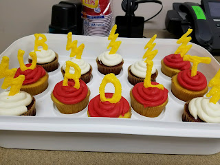 red and gold cupcakes with chocolate toppers spelling out BU BOLT