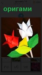 Из бумаги собраны методом оригами два тюльпана красного и белого цвета с зелеными лепестками