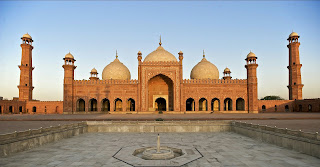 """The gem of the city of Lahore, Badshahi Masjid was built by the Sixth Mughal Emperor Aurangzeb Alamgir in the year 1673. The construction of the masjid started in 1671 and completed in 1673. It was designed after the Jamia Masjid of Delhi which was constructed by Aurangzeb's father Emperor Shah lahan in 1648 A.D. It epitomizes the beauty, passion and grandeur of the Mughal era.  Inscribed in a marble tablet on the entrance of Badshahi Masjid are the following words in the Persian language: """"The Masjid of Abul Muzaffar Muhy-ud-Din Muhammad Aurangzeb Alamgir,Victorious King, constructed and completed under the superintendence of the Humblest Servant of the Royal Household, Fidai Khan Koka,""""   Badshahi Masiid was built in front of Lahore Fort, emphasizing its stature in the Mughal Empire. It was constructed on a raised platform to avoid inundation from the nearby River Ravi during flooding season. The Masjid's foundation and structure were constructed using bricks and compacted clay. The structure was then covered with red sandstone tiles brought from a stone quarry near jaipur in Rajistan and its domes were covered with white marble. The Masjid has the capacity of accommodating 5,000 worshipers in its main prayer hall and an additional 95,000 in its courtyard and covered pillared passages.  The exterior walls of Badshahi Masjid are decorated with sculptured panels. In each corner of the Masjid there is a minaret which is sauare in shape and one hundred and seven feet high. Each tower has two hundred and four steps.  There is a small museum above the gate in the chambers. The relics displayed there are attributed to the Rasoolullah(ﷺ), his daughter Hazrat Fatima Tuz-ahara and his son-in-law Hazrat Ali. These relics were brought to the sub-continent by Amir Taimoor. They include: a cap, white trousers, a green coat, a slipper worn by Hazrat Muhammad(ﷺ), the mark of his(ﷺ) foot prints impressed on a sand coloured stone and his banner with the verses of the Holy Quran on """