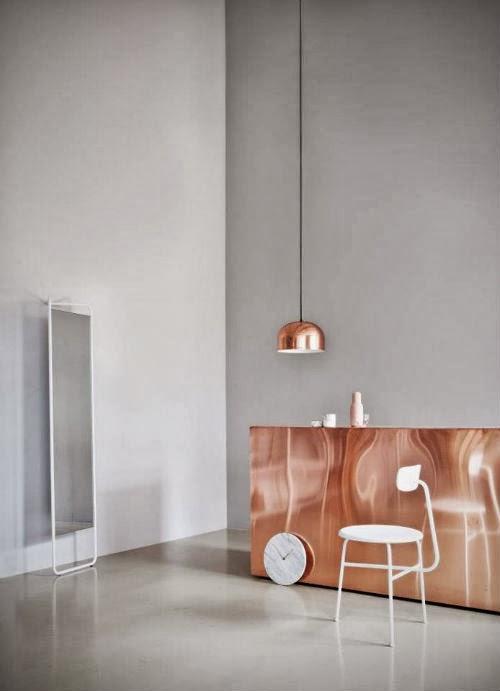 Im neuen Showroom hängt eine kupferfarbene Lampe über einem Thresen in Kupfer