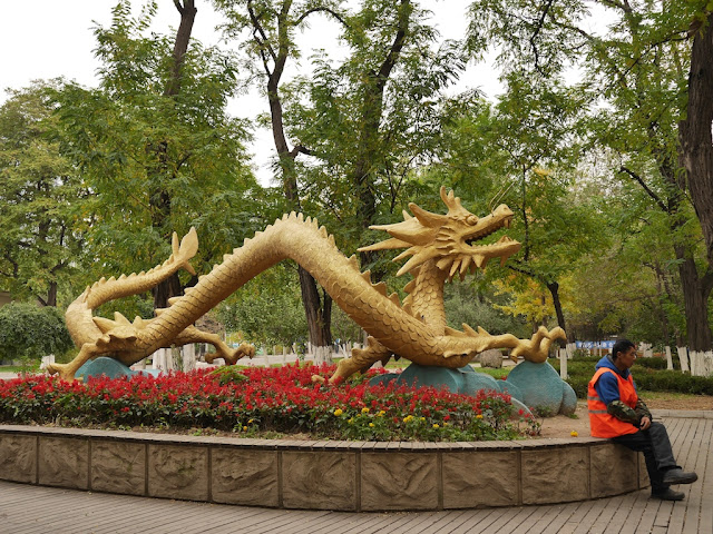 Man sitting with a large sculpture of a Chinese dragon immediately behind him
