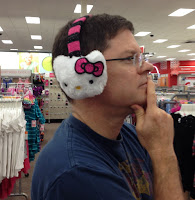 David Borden wearing some very attractive Hello Kitty ear muffs and pondering whether to Make More Decisions with Your Heart