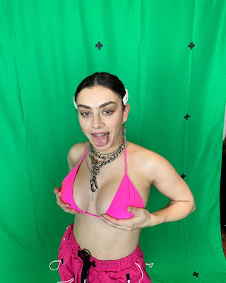 Charli XCX poking out her tongue with her hands under her breasts in a neon pink bikini top