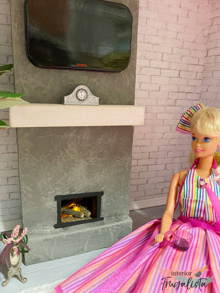 How to build a miniature dollhouse plaster fireplace with real logs and child-safe flickering flame, plus a DIY flat-screen television to hang above.