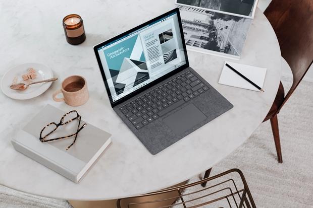 Mesa de trabalho matinal com caneca, livro, óculos, caneca e prato e notebook sobre uma mesa